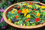 Salad leaves, nasturtium and courgette flowers in wooden bowl