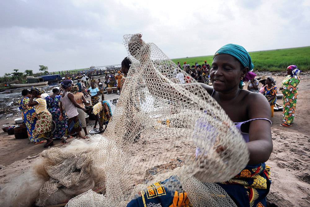 Beninese women mending her net along the lagoon of Ganvie in Cotonou, Benin March 1, 2008.