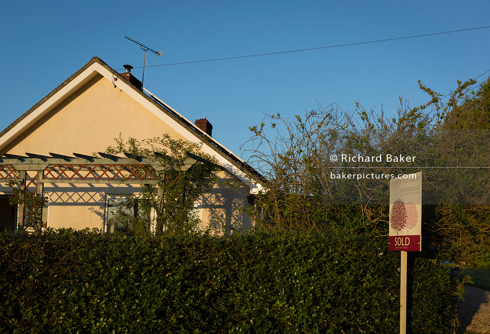 A Sold sign from a local north Somerset estate agency outside a rural bungalow, on 5th May 2018, in Wrington, North Somerset, England.