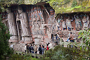 Tourist look at Anicca, God of Destiny holding wheel of life, Dazu rock carvings, Mount Baoding, China