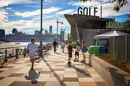 Pier 25 on west side of Manhattan at Hudson River Park.  Pedestrians walk and skate along pier, outside the entrance to Mini Golf, as cruise ship passes