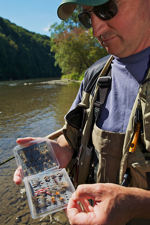 Jeremy Lucas (Pioneer Flyfishing Ltd) examining his flybox at the San River. Myczkowce, Poland.