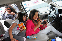 In the car, often their mobile home, three of the girls play. From left, Brisa Garcia, 12, gathers her things for sleeping in the shelter, while sisters Jenifer, 5, and Iris, 11, check out the info on someone's phone.