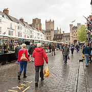 a street market in the Market Place in the center of Wells, Somerset, near Wells Cathedral (visible in the background).