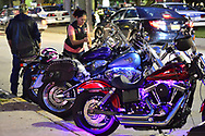 Bellmore, New York, USA. 11th August 2017. Motorcyclist locks up her parked Harley Davidson motorcycle parked with other motorcycles across the street from Bellmore Friday Night Car Show, in parking lot of LIRR Bellmore station.