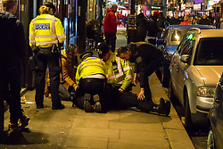 London, January 01 2018. XPolice attend to a man on Old Compton Street who appeared to have had a seizure as revellers in London's West End enjoy New Year's Eve. © SWNS