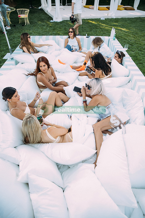 """Kourtney Kardashian opened up her palatial Calabasas home to host a swanky party for her newly-founded lifestyle blog, Poosh. The 40-year-old mother-of-three, who launched her blog earlier this year, was joined by her mother Kris Jenner along with a slew of celebs including Rosie Huntington-Whiteley, Suki Waterhouse, Adrienne Bailon, Rachel Roy, Malika and Khadijah Haqq, Nicole Williams, Simi and Haze Khadra, Melissa Alcantara and Yris Palmer. Guests received a hotel-like experience for the day as they were given a map of activities, picked out a swimsuit from Onia, slipped into a robe from Brooklinen, and popped by the Stuart Weitzman clubhouse for custom sneakers. Guests booked facials from Peach & Lily and massages from Squeeze, which were located on Kourtney's basketball court on Avocado Mattresses. Gymshark provided a shaded cabana oasis for a yoga class led by master trainer, Melissa Alcantara (@FitGurlMel). She took them through an energizing flow as they donned the Gymshark poise leggings and bralette tops in a mint shade that perfectly fit the event aesthetic. After yoga, attendees enjoyed a tea ceremony led by Shiva Rose to celebrate the full moon. Elle Macpherson's WelleCo offered naturopathic consultations from Dr. Simoné Laubscher along with a full elixir bar with smoothies and frozen yogurt made with their plant-based protein powder. To make sure guests were super chilled out, Hemple created CBD cocktails including """"Love Shots"""" boosted with Hemple Sigma, crushed strawberries, cloudy apple juice, rosemary, and lime. Food was all organic and gluten-free catered by Bread and Wine. Guests enjoyed refreshing mini Tequila Don Julio Blanco margaritas and toasted the evening with custom Poosh engraved Don Julio 1942 bottles. The Poosh team toasted with Winc's Summer Water, Poosh Please Skinny Margaritas and Poosh-Perfect Paloma cocktails. For dessert, we cooled down with vegan treats from Dream Pops. Slip Silk staged a massive pillow pit, which was a hi"""