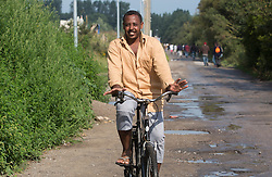 "© Licensed to London News Pictures. 30/08/2015. Calais, France. A refugee rides a bike to move around the camp, also known as the Jungle, at Calais. Today around a hundred British cyclists from ""Bikes Beyond Borders"" arrived at the refugee camp in a two-day ride from London to donate bicycles and supplies to support the life at the site. Photo credit : Isabel Infantes/LNP"