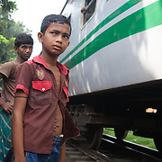 Life in the slums by the  railway tracks in Tejgaon. Homes are build closely to the tracks leading in and out of one of Dhaka's main train stations and life is goes on as in any othr part of Dhaka in spite of the dangerous proximity to the live tracks and trains passing at regular intervals. Children are waiting for a train to pass.
