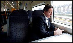 The Leader of Conservative Party David Cameron checks his europe speech on his blackberry on the train after speaking to employees at Morrisons distribution centre in Sittingbourne, Kent, Monday March 29, 2010. Photo By Andrew Parsons / i-Images