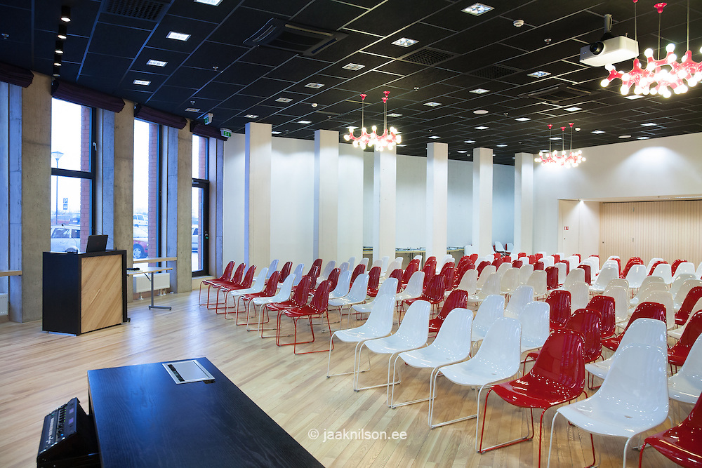 Modern large conference hall with lectern, podium and table. Colorful chairs row in university auditorium. Tartu Health Care College in Estonia.