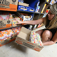 Nicole McLaughlin takes time Thursday morning to stock the shelves at the food pantry located at Shannon Elementary School.