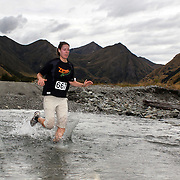 Runner Jeska Grave crosses Moke Creek on the Ben Lomond High Country Station during the Pure South Shotover Moonlight Mountain Marathon and trail runs. Moke Lake, Queenstown, New Zealand. 4th February 2012. Photo Tim Clayton