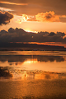 Sunrise orange reflections seen from Sanur Beach in Bali, Indonesia