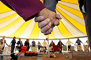 Church members hold hands while praying in a circle during services under a newly erected tent for the All Tribes Community Church in east Tulsa, OK, March 18, 2007.