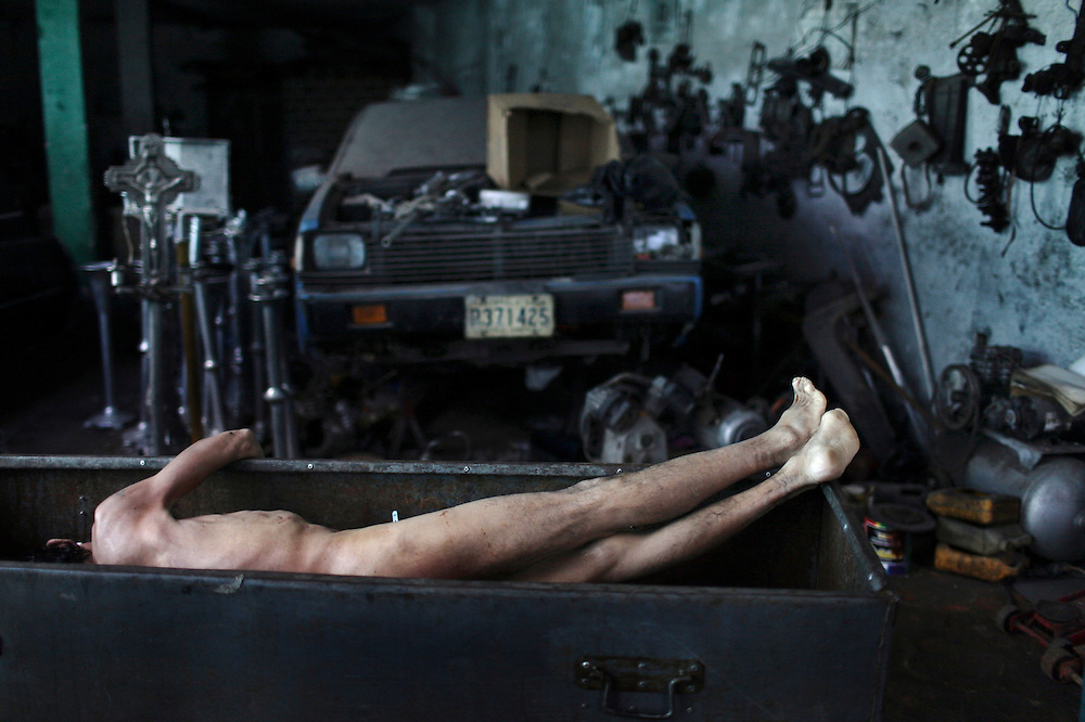 "The body of a man is seen inside a metal box, left there while funeral home employees took a break from the embalming process at ""Valle del Sol"" funeral home in Guatemala City, Tuesday, Nov 17,  2009. Guatemala's constant streak of murders ,17-a-day,  provide a steady flow of customers to unregulated  funeral homes, where funeral workers can embalm corpses in the back of auto repair shop or rush to crime scenes to gather information that will allow them to locate, notify and make a sales pitch to the bereaved relatives."