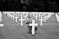 A worker doing maintenance work on a headstone at The Luxembourg American Cemetery and Memorial, the burial area of 5,076 military dead during the Second World War. Photo: ©Erik Luntang