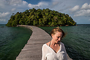 A guest walks across the boardwalk connecting the two islands that make up the Song Saa resort.