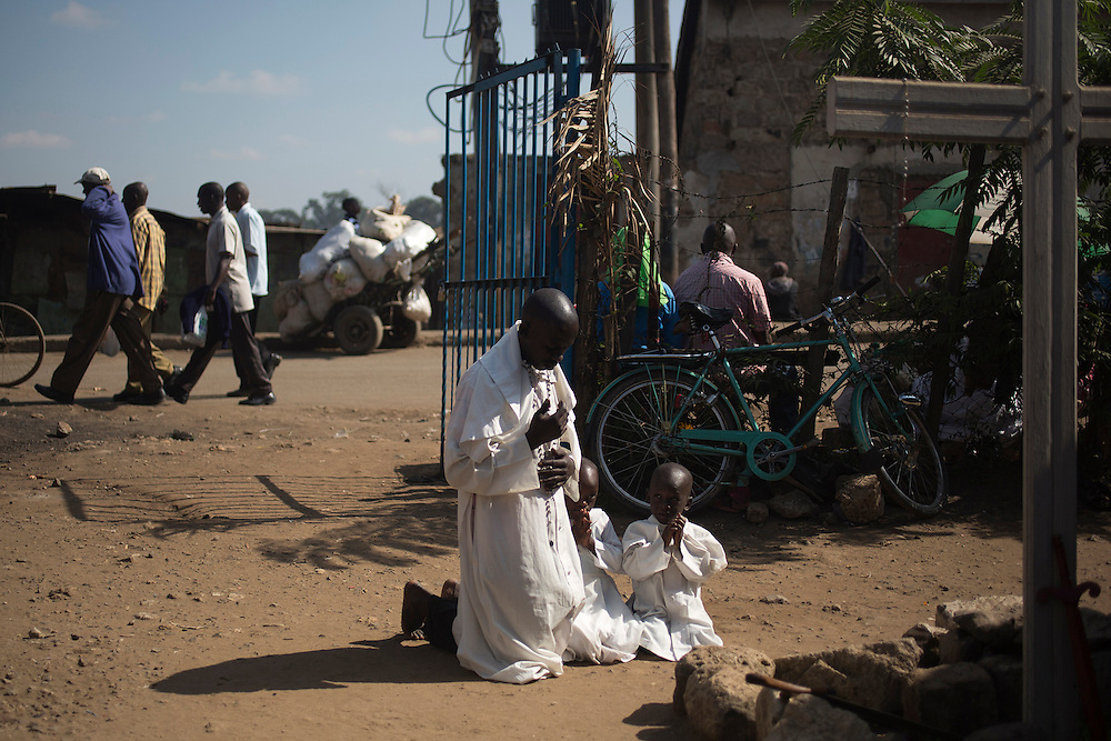 A member of the religious following the Legion of Mary and his children pray by a cross near the gate of their church during Sunday mass in the slum of Korogocho, Nairobi.