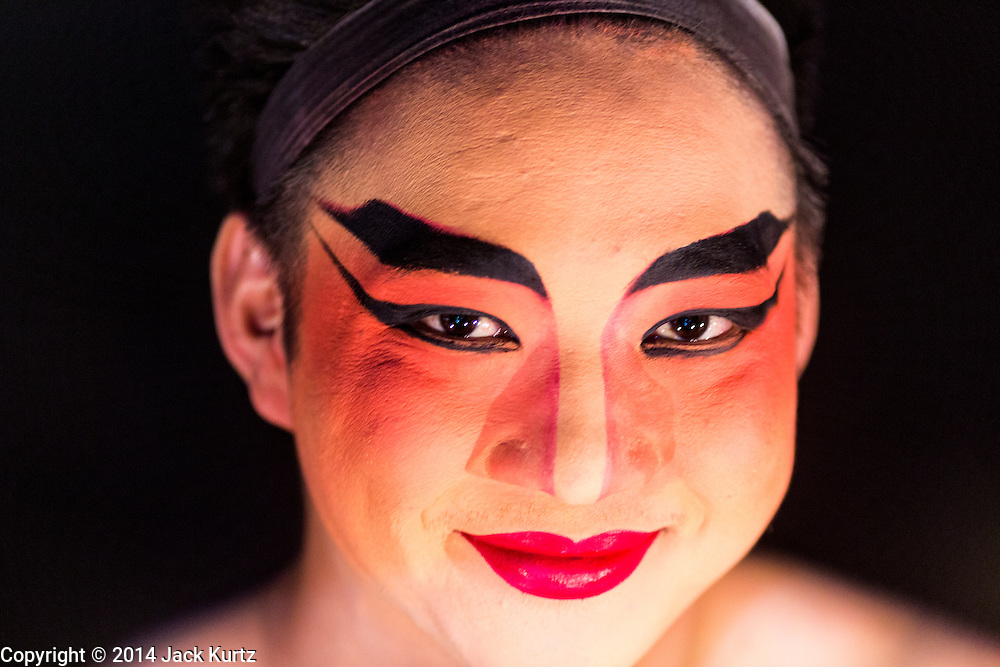 "28 JANUARY 2014 - BANGKOK, THAILAND: A performer with the Tear Kia Ee Lye Heng opera troupe before a show. They were performing for a business in the Min Buri district of Bangkok for the Lunar New Year, which this year is Jan 31. Chinese opera was once very popular in Thailand, where it is called ""Ngiew."" It is usually performed in the Teochew language. Millions of Teochew speaking Chinese emigrated to Thailand (then Siam) in the 18th and 19th centuries and brought their cultural practices with them. Recently the popularity of ngiew has faded as people turn to performances of opera on DVD or movies. There are still as many 30 Chinese opera troupes left in Bangkok and its environs. They are especially busy during Chinese New Year when they travel from Chinese temple to Chinese temple performing on stages they put up in streets near the temple, sometimes sleeping on hammocks they sling under their stage. They are also frequently hired by Chinese owned businesses to perform as a form of merit making.    PHOTO BY JACK KURTZ"