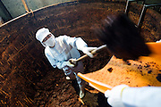 A company employee shovels out Hatcho miso paste from the giant vats  at Maruya Hatcho Miso Co.'s factory in Okazaki City, Aichi Prefecture Japan on 11 Dec. 2012. Hatcho miso has been made continuously by the company since 1337. Photographer: Robert Gilhooly