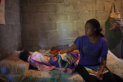 Rosaline Centeno sits with her 16-year old daughter at their home on January 15, 2013 in San Juan, Honduras.  Her daughter has HIV and refused to take her medicine for several years, leading to severe health complications. Stigma is a big problem in the Garifuna community, leading some people to deny their HIV diagnosis.  (David Rochkind/ Pulitzer Center)