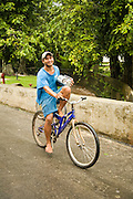 Man riding bycle with radio, Huahine, French Polynesia