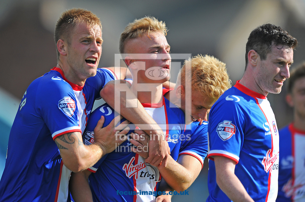 Kyle Dempsey of Carlisle United (centre) is congratulated by team-mates after scoring his team's second goal during the Sky Bet League 2 match at Brunton Park, Carlisle<br /> Picture by Greg Kwasnik/Focus Images Ltd +44 7902 021456<br /> 06/09/2014