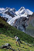 "A trekker ascends steep terrain below glaciers flowing from Yerupaja Grande (right, west face, 6635 m or 21,768 ft), the second-highest peak in Peru, highest in Cordillera Huayhuash, and highest point in the Amazon River watershed (which is on the other side of the mountain). At left is Mount Jirishanca, or the ""Icy Beak of the Hummingbird"" (6126 m or 20,098 feet elevation) in the Andes Mountains, Peru, South America. We trekked from here on the Pacific side around to the Amazon River watershed side."
