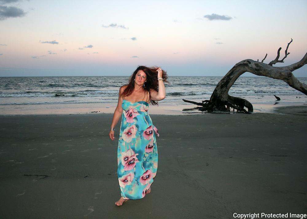 Red head woman walking Jekyll Island Driftwood Beach at sunset
