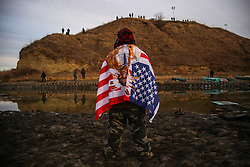 November 25, 2016 - Cannon Ball, North Dakota, U.S - JARED KOPADDY of the Comanche Nation in Oaklahoma stands as he faces authorities on the other side of the Missouri River after barbed wire was placed along the shore near the Oceti Sakowin Camp at the Standing Rock Indian Reservation in Cannon Ball, North Dakota. ''This is my very first time of being scared of being here...all I have to say is pray, just pray,'' said KOPADDY. (Credit Image: © Joel Angel Ju‡Rez via ZUMA Wire)