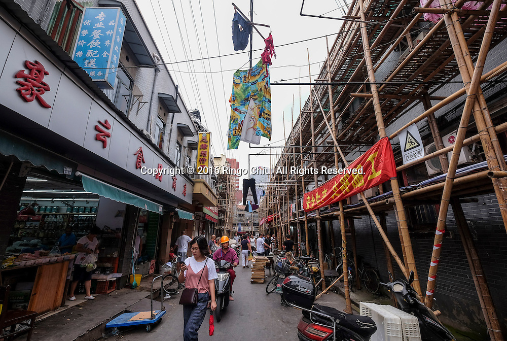 A view of an old alley off of the Nanjing Road Pedestrian Street in Shanghai, China. Shanghai is the most populous city in China and the most populous city proper in the world. It is one of the four direct-controlled municipalities of China, with a population of more than 24 million as of 2014. It is a global financial centre, and a transport hub with the world's busiest container port. Located in the Yangtze River Delta in East China, Shanghai sits on the south edge of the mouth of the Yangtze in the middle portion of the Chinese coast. The municipality borders the provinces of Jiangsu and Zhejiang to the north, south and west, and is bounded to the east by the East China Sea. A major administrative, shipping, and trading town, Shanghai grew in importance in the 19th century due to trade and recognition of its favourable port location and economic potential. The city was one of five forced open to foreign trade following the British victory over China in the First Opium War while the subsequent 1842 Treaty of Nanking and 1844 Treaty of Whampoa allowed the establishment of the Shanghai International Settlement and the French Concession. The city then flourished as a center of commerce between China and other parts of the world (predominantly Western countries), and became the primary financial hub of the Asia-Pacific region in the 1930s. However, with the Communist Party takeover of the mainland in 1949, trade was limited to socialist countries, and the city's global influence declined. In the 1990s, the economic reforms introduced by Deng Xiaoping resulted in an intense re-development of the city, aiding the return of finance and foreign investment to the city. Shanghai has been described as the &quot;showpiece&quot; of the booming economy of mainland China; renowned for its Lujiazui skyline, museums and historic buildings, such as those along The Bund, the City God Temple and the Yu Garden.(Photo by Ringo Chiu/PHOTOFORMULA.com)<br /> <br /> Usage Notes: This content is intended for edi