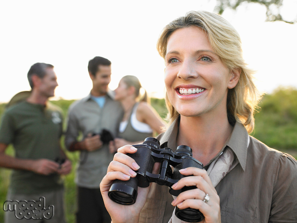 Portrait of adult woman holding binoculars smiling others in background