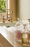 Bottles of Bath Oils on edge of bathtub filled with bubbles water running from tap