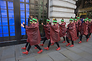 Dancers march along the street before performing for the UK company Hunter perform a choreographed dance routine to officially launch the brand's flagship new store in London's Regent Street. Twenty Eight dancers stopped shoppers with their production of 'Singin' in the Rain.'