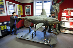 © Licensed to London News Pictures. 10/12/2012. London, UK. Two Bonham's employees move a large latex prop shark (est. £1000-1500) used in the 2010 'Doctor Who' Christmas Special 'A Christmas Carol' at an auction press view in Knightsbridge, London, today (10/12/12). The entertainment memorabilia auction, set to take place at Bonham's Knightsbridge auction house on the 12th of December, features props and costumes from film and TV as well as important Beatles pieces. Photo credit: Matt Cetti-Roberts/LNP