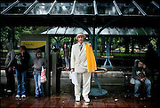 "Duke of the Realm Richard ""Dick"" B. Clifton, a member of the Royal Rosarians, ambassadors of goodwill for the city of Portland, Ore., waited for a light rail train in the rain after the city's Rose Parade in June."