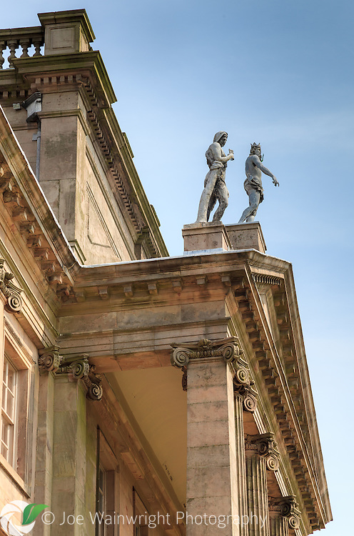 Two of the three lead statues, standing on the pediment of the mansion at Lyme Park, Disley Cheshire.  They are  Pan (left) and Neptune.