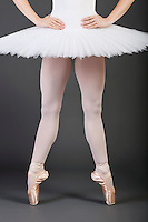 Low section of young female ballet dancer wearing white tutu and ballet slippers
