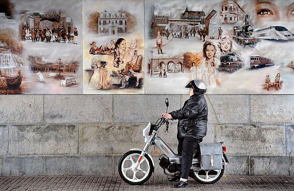 Nederland, Arnhem, 25-3-2009Een vrouw op een brommer schuilt onder het treinviaduct tegen de regen. Op de muur zijn muurschilderingen aangebracht.Foto: Flip Franssen/Hollandse Hoogte
