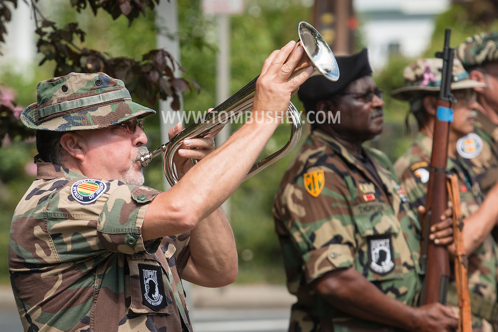 """Middletown, New York - A veteran plays """"Taps"""" during  in the Middletown-Town of Wallkill Memorial Day parade and ceremonies on  May 25, 2015."""