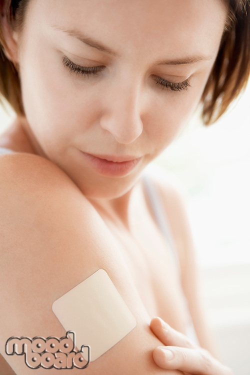 Woman looking at nicotine patch on arm close up