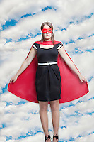 Portrait of young woman in superhero costume against cloudy sky