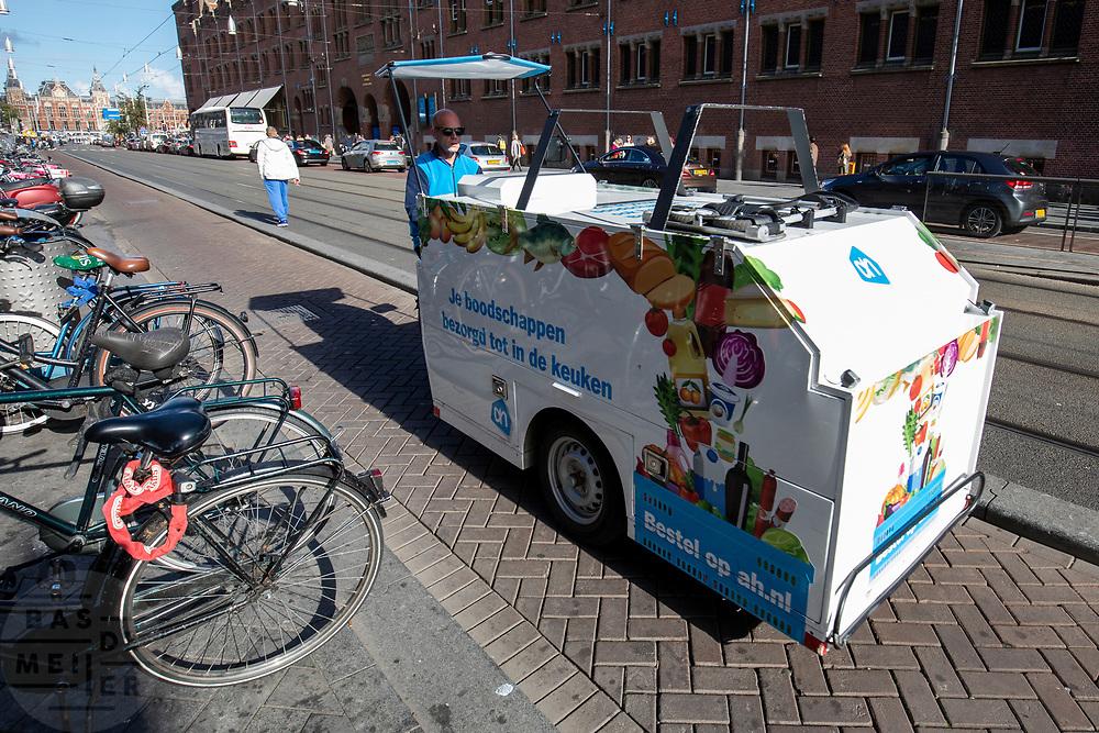 In Amsterdam rijdt een grote bakfiets van de bezorgdienst van Albert Heijn over het Damrak.<br /> <br /> In Amsterdam a cargo delivery bike of supermarket Albert Heijn rides at the Damrak.