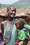 Maasai woman wearing traditional beads jewelry holds a child, Photographed in Kenya