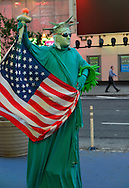 NYC, New York, U.S.  21st May 2013. This person is dressed in a green Statue of Liberty costume and carrying an American flag, during a pleasant spring day, with a high of 86ºF/32ºC in Manhattan.