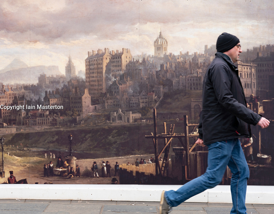 Man walks past billboard at building site of  renovation construction work of Royal Scottish Academy and Scottish National Gallery art museums on The Mound in Edinburgh, Scotland, UK