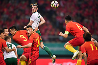 Gareth Bale, top, of Wales national football team heads the ball to make a pass against players of Chinese national men's football team in the semi-final match during the 2018 Gree China Cup International Football Championship in Nanning city, south China's Guangxi Zhuang Autonomous Region, 22 March 2018.