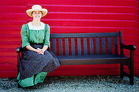 Farm girl sits on bench wearing period costume, Motherwell Homestead National Historic Site, Saskatchewan