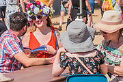 Planning for the day using the show guide. It is so hot today that all the shade trees can provide is used and there is a wide range of headgear for those in the sun - The 2018 Latitude Festival, Henham Park. Suffolk 15 July 2018